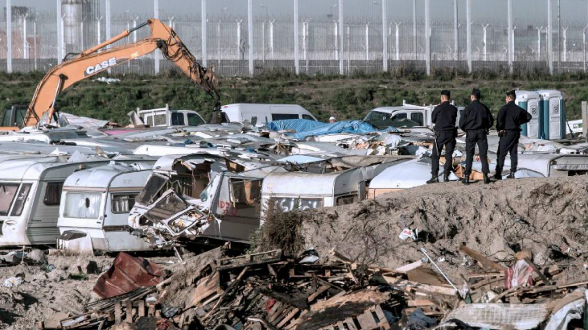 Tres agentes de seguridad observan la demolición de parte del campamento de refugiados francés conocido comom 'La Jungla' de Calais. AFP
