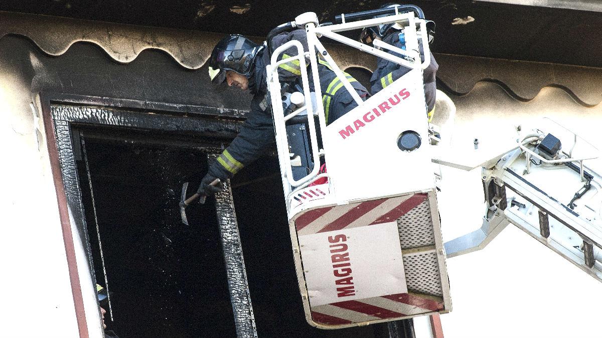 Un bombero ante la ventana de la vivienda incendiada (Foto: Efe).
