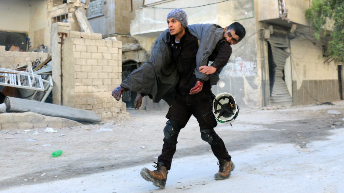 Un hombre carga con un herido por las calles de Alepo, tras los bombardeos del régimen de Assad. (AFP)