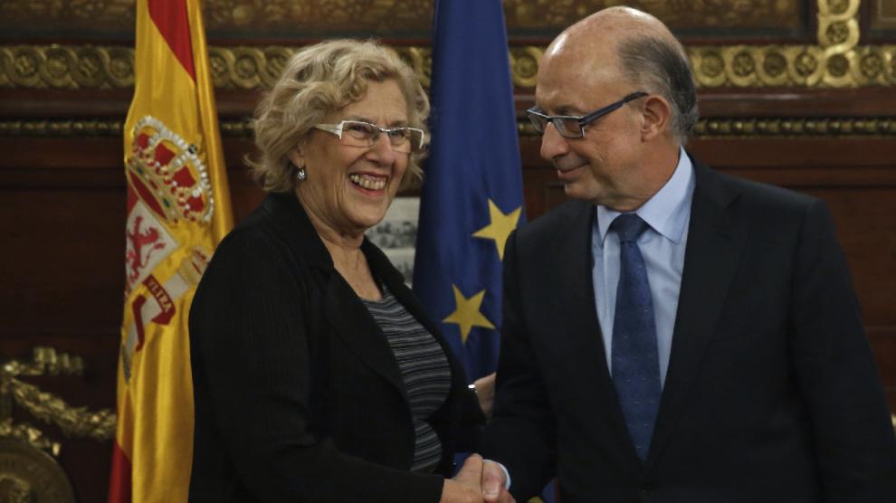 La alcaldesa de Madrid, Manuela Carmena (i), saluda al ministro de Hacienda y Función Pública, Cristóbal Montoro. (Foto: EFE)