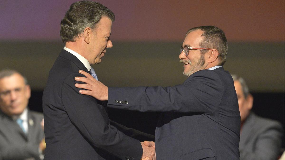 Juan Manuel Santos estrecha la mano del terrorista 'Timochenko'. (Foto: AFP)