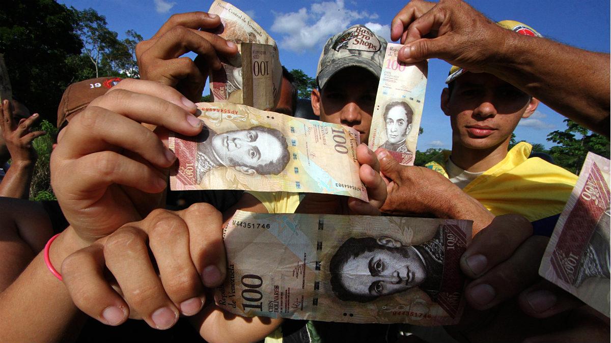Venezolanos haciendo cola para cambiar sus billetes de 100 bolívares. (AFP)