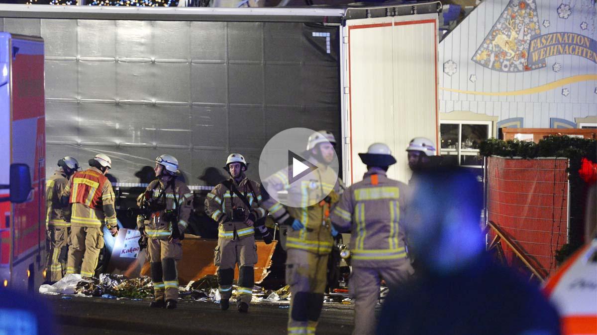 Varios bomberos junto a los restos de varias víctimas atropelladas por el camión. (Foto: AFP)