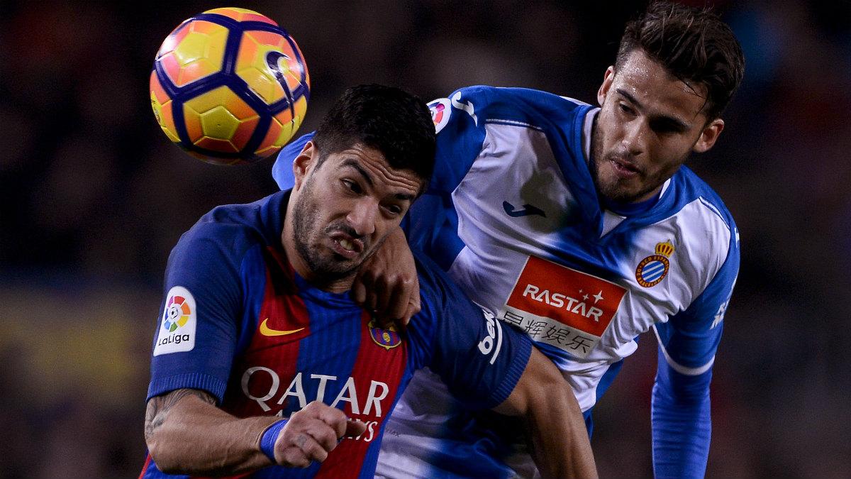 Luis Suárez y Diego Reyes pelean por un balón durante el Barcelona-Espanyol. (AFP)