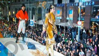 Un domador domina con latigazos a una chica vestida de leona en la Cabalgata de Barcelona.