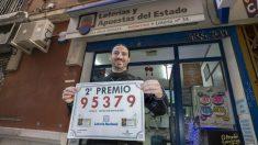 El gerente de la administración de loterias La Bruja Rockera, la número 34 de Murcia, José María Imbernon, muestra el cartel del segundo premio del sorteo del niño, el 95.379, del que ha vendido un número agraciado con 75.000 euros, hoy en la calle Azucaque de Murcia. Foto: EFE