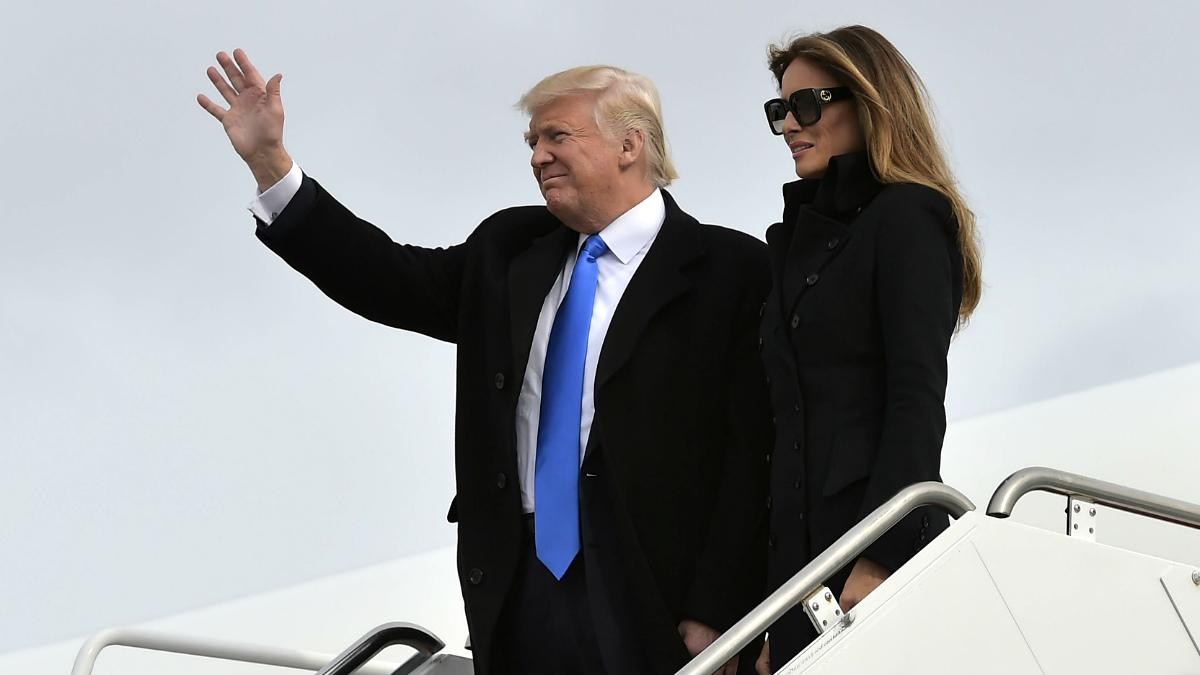 Donald Trump, junto a su esposa, saluda a su llegada al aeropuerto de Washington. (AFP)