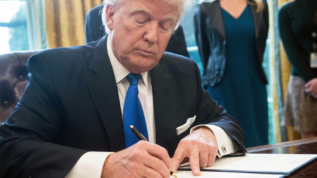 Donald Trump firma un decreto en el despacho oval de la Casa Blanca. (Foto: AFP)