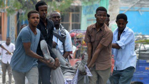 Vecinos de Mogadiscio cargan con un herido en el atentado del hotel Dayax. (Getty)