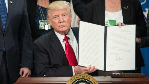 Donald Trump exhibe su enorme firma tras la firma de un decreto en el despacho oval de la Casa Blanca. (AFP)
