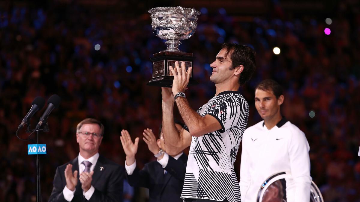 Federer levanta el trofeo de campeón del Open de Australia, con Nadal en segundo plano. (Getty)