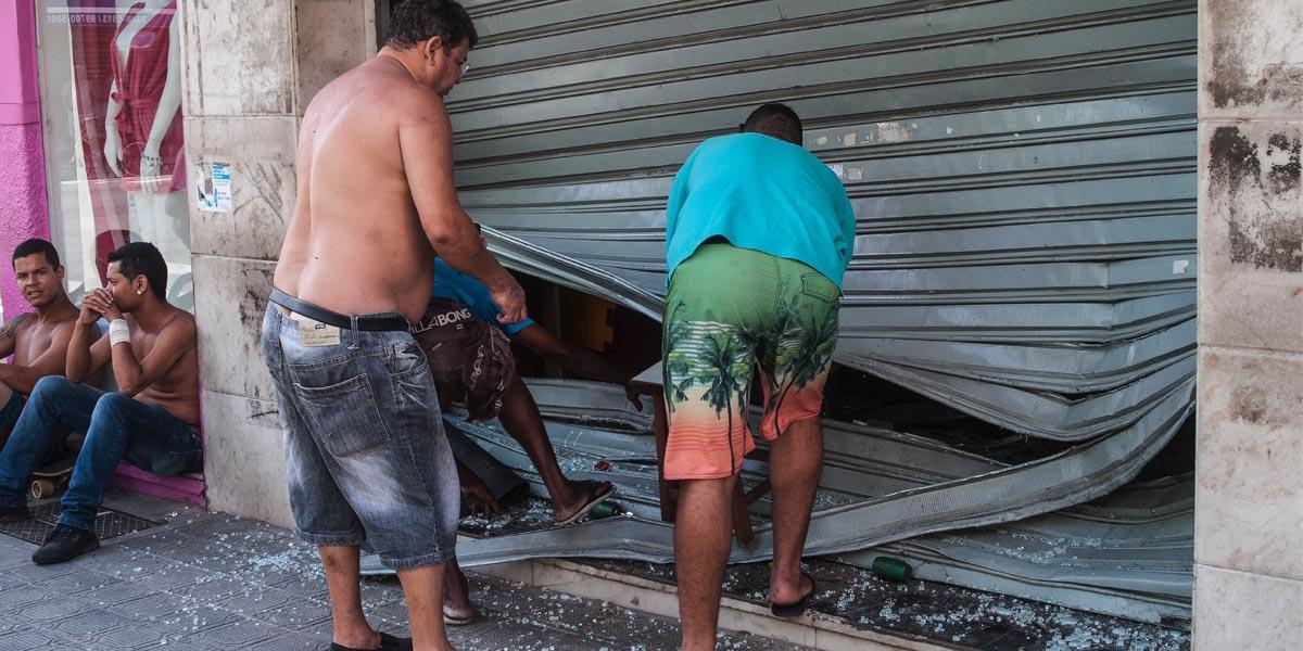 Unos hombres arreglan el cierre de una tienda saqueada cerca de Vitoria, capital del estado de Espírito Santo. (Foto: AFC)