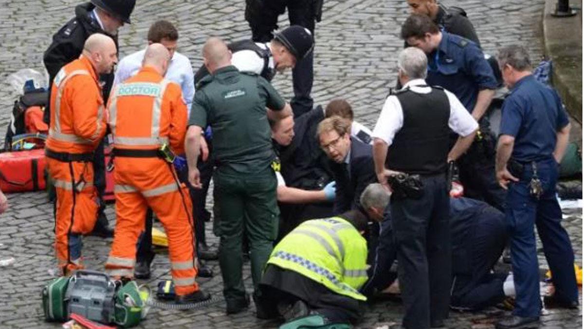 Tobias Ellwood, en el centro, atiende al agente herido (Foto: The Telegraph)