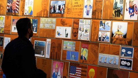 """Un visitante observa varios """"retratos"""" de Donald Trump en el Salón del Cómic de Barcelona (Foto:EFE)"""