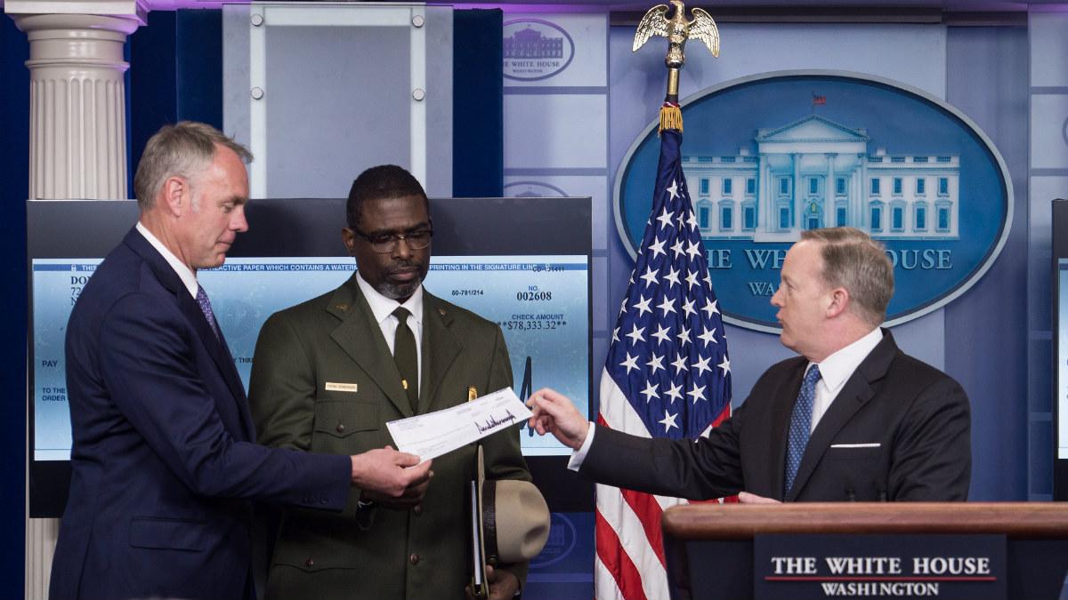 El portavoz de la Casa Blanca, Sean Spicer, entrega al secretario de Interior, Ryan Zinke, el primer cheque del salario del presidente de Estados Unidos, Donald Trump, donado al Servicio Nacional de Parques (Foto: AFP)