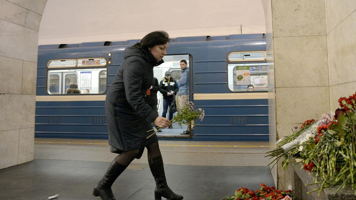 Una mujer deposita flores donde sucedió la masacre en el metro de San Petersburgo (AFP)