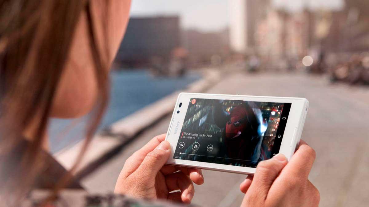 Una joven ve una serie en su móvil