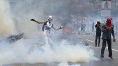 Un manifestante devuelve un bote de gas lacrimógeno lanzado por la policía. (Foto: AFP)