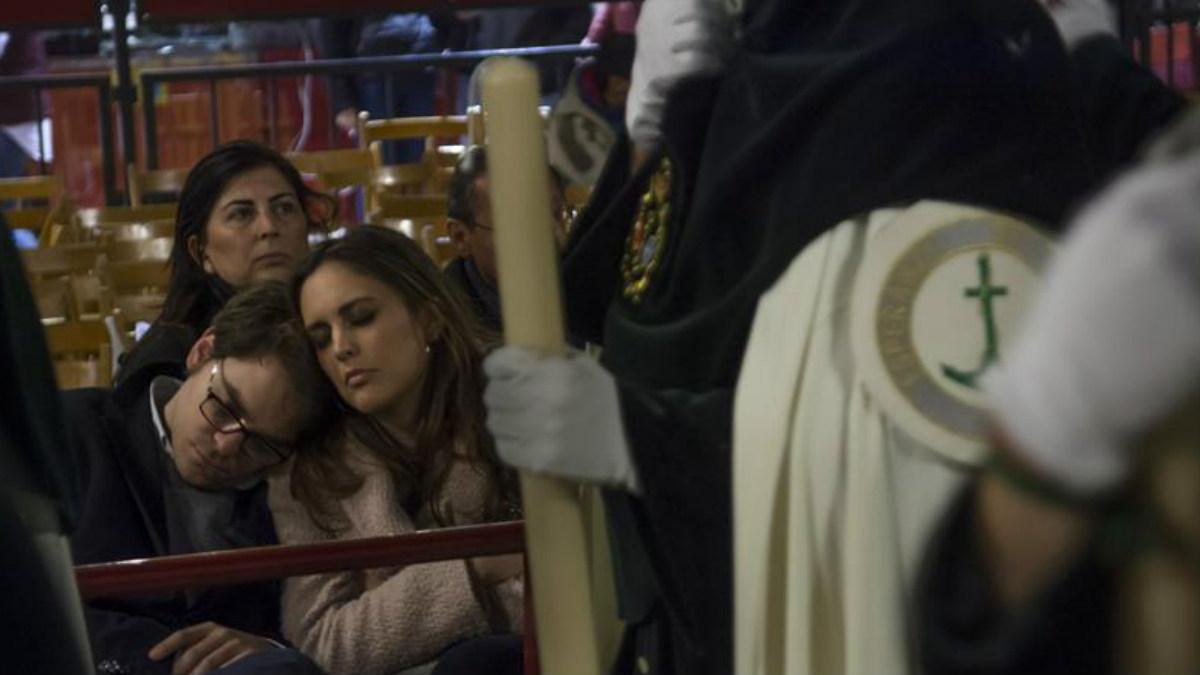 Una pareja descansa mientras los nazarenos de la Esperanza de Triana pasan por la Carrera Oficial, esta noche durante la Madrugá de Sevilla. Foto: EFE