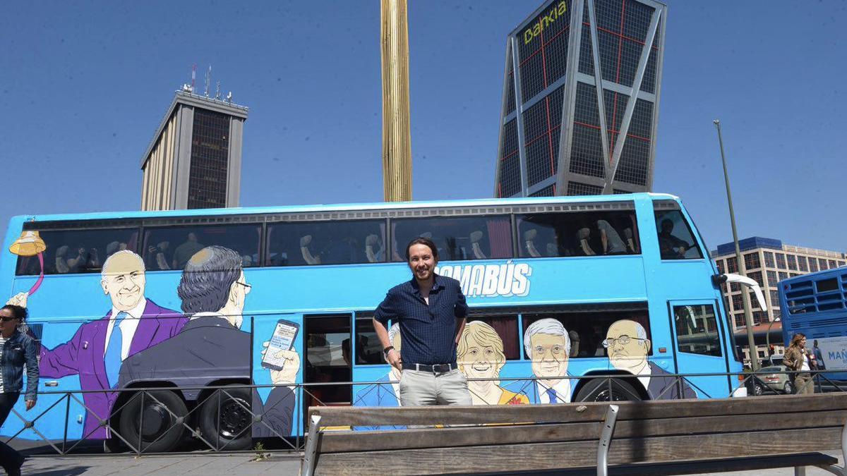 El líder de Podemos, Pablo Iglesias, con su 'tramabus' frente a la sede de Bankia. (Foto: TW)