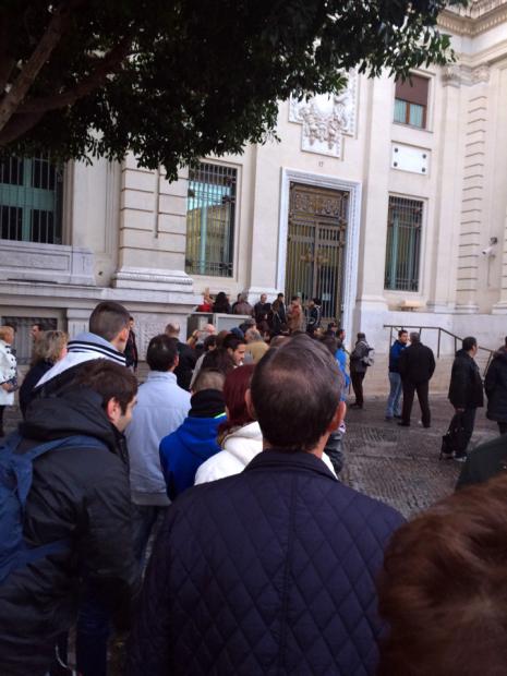 Banco de España de Sevilla, cola antes de apertura de personas pagadas para extraer moneda española