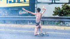 Un manifestante se enfrenta a las fuerzas de seguridad de Maduro en Caracas. (AFP)