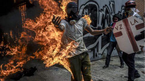 Un manifestante anti Maduro sale ardiendo tras una carga policial en Caracas. (AFP)