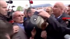 Marine Le Pen, protegida por su equipo de seguridad mientras varios manifestantes le lanzan huevos