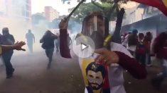 Lilian Tintori, con máscara antigás, enarbola una bandera venezolana ante la represión de las fuerzas de Maduro.