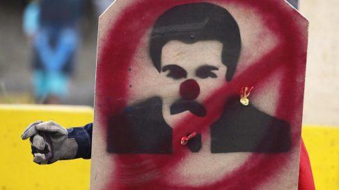 Un manifestante con un 'escudo' con una pintada que ridiculiza a Nicolás Maduro. (Foto: AFP)