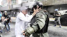 Un médico trata de hablar con un agente en una de las protestas en Caracas. (Foto: AFP)
