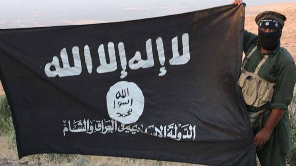 Un terrorista sostiene el emblema del autodenominado Estado Islámico (ISIS).
