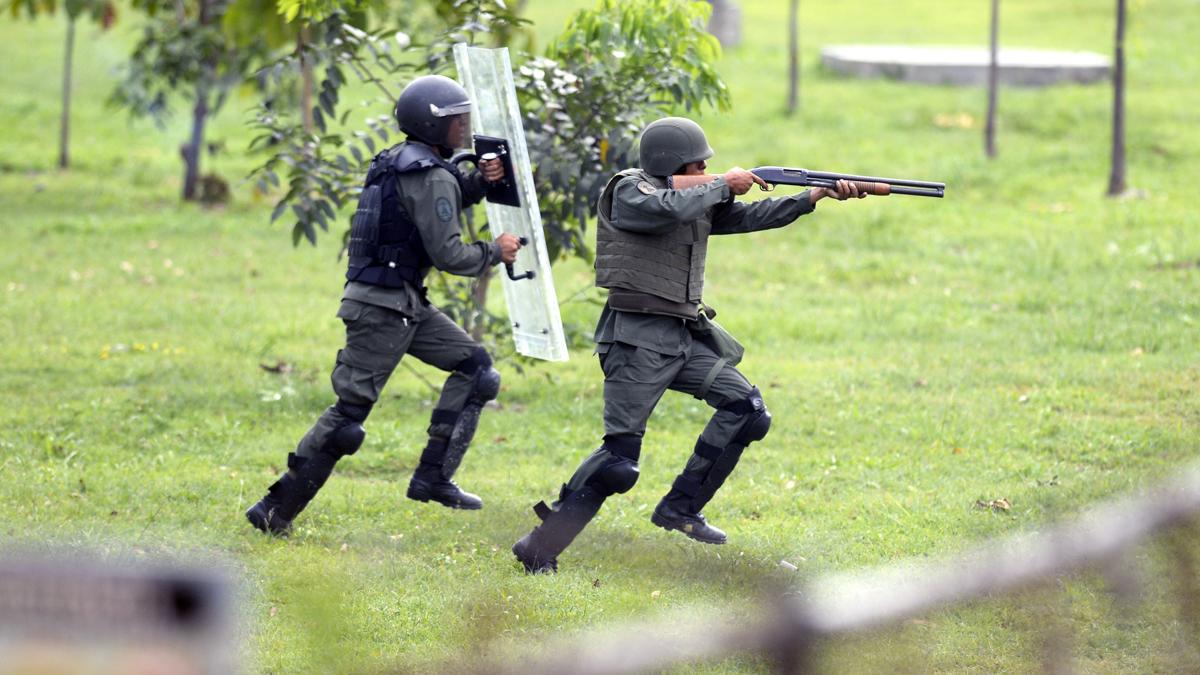 Fuerzas del Gobierno de Nicolás Maduro apuntando a manifestantes. (Foto: AFP)