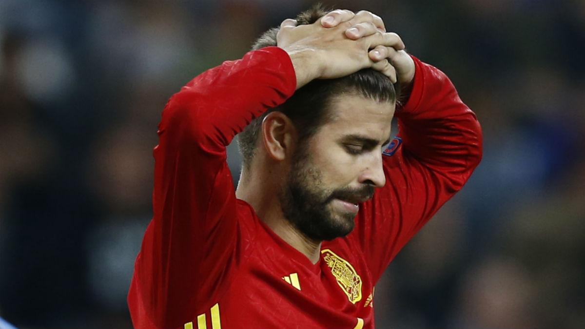 Piqué se lamenta durante un partido de España. (AFP)