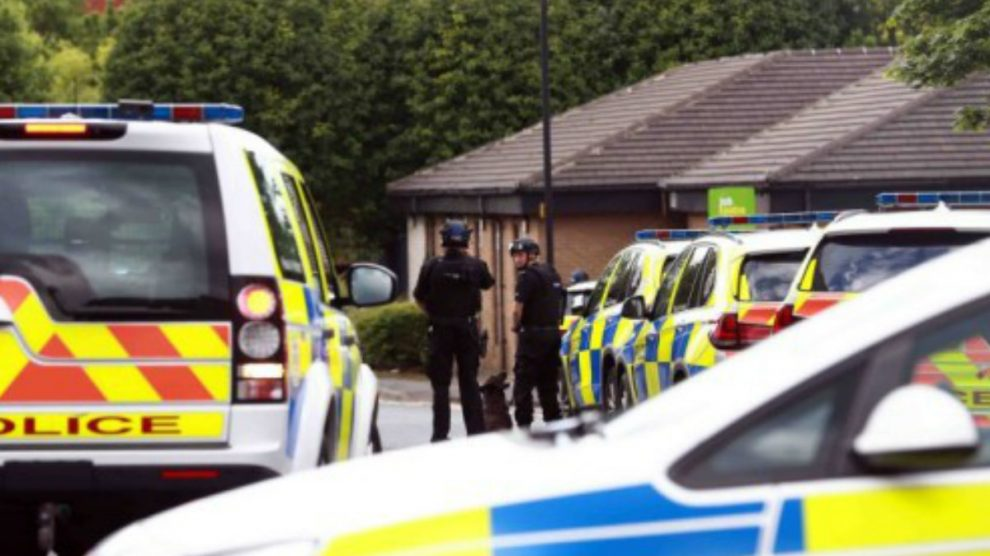 AGentes de la policía de REino Unido afuera de la oficina de empleo secuestrada.