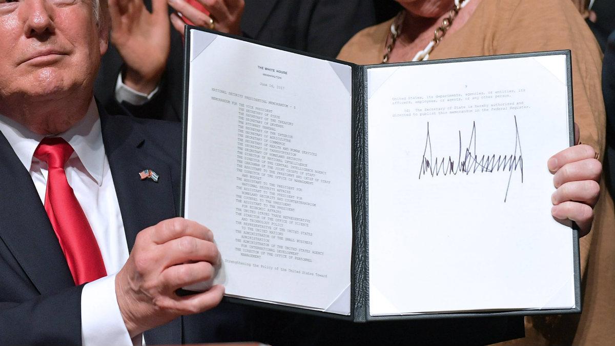 Trump muestra orgulloso su enorme firma en el decreto para frenar el deshielo con Cuba, en el teatro Manuel Artime de Miami. (AFP)