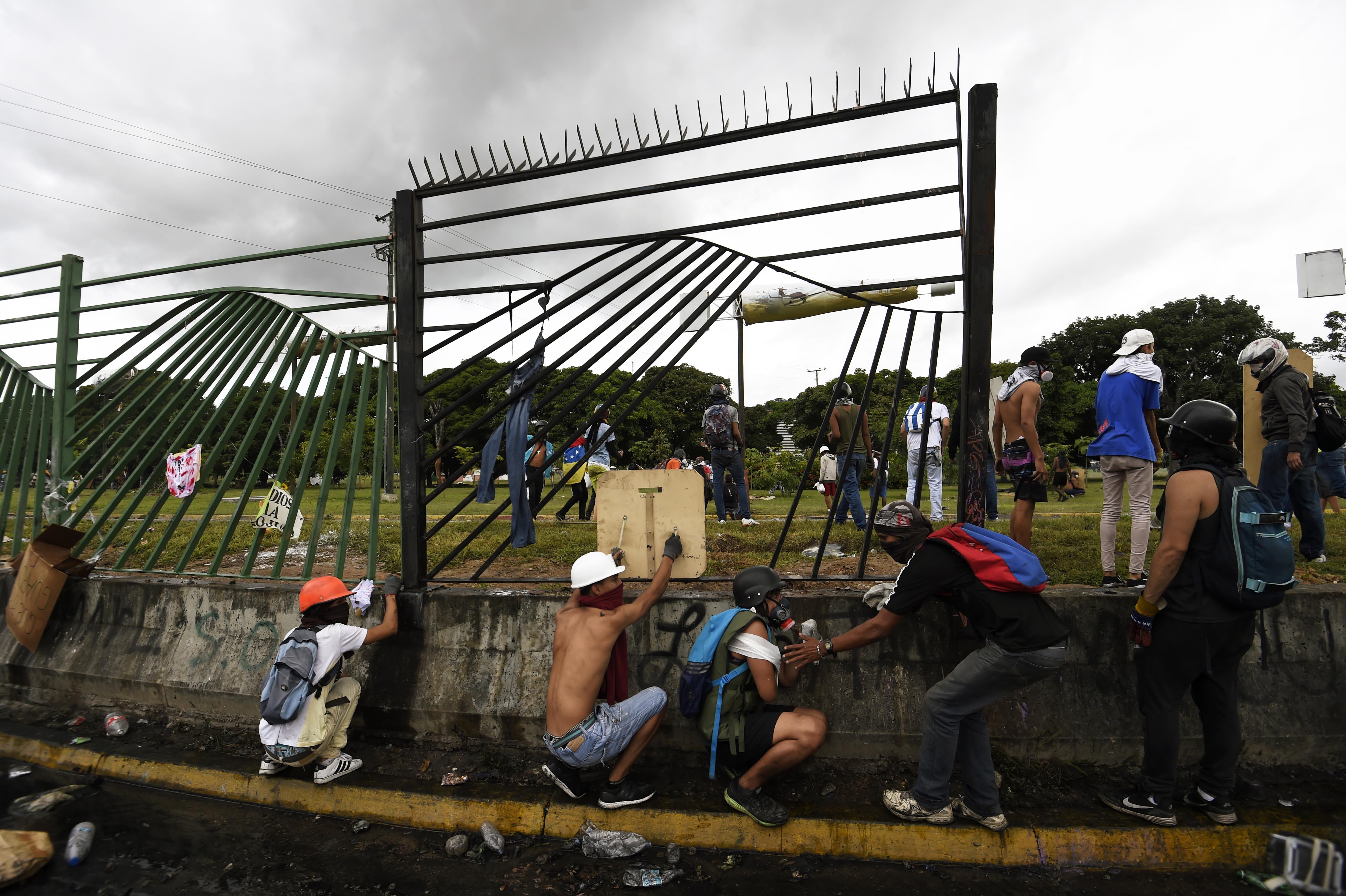 Opositores venezolanos protestan en la valla de la base aérea Francisco de Miranda. (Foto: AFP)