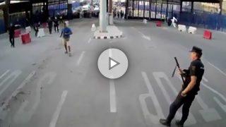 Agentes de la Policía Nacional española momentos antes de reducir al agresor de la frontera con Melilla, ataviado con camiseta azul.
