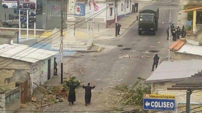 Los dos sacerdotes se acercan las manos en alto a los agentes de Maduro para intentar frenar la represión de los enfrentamientos.