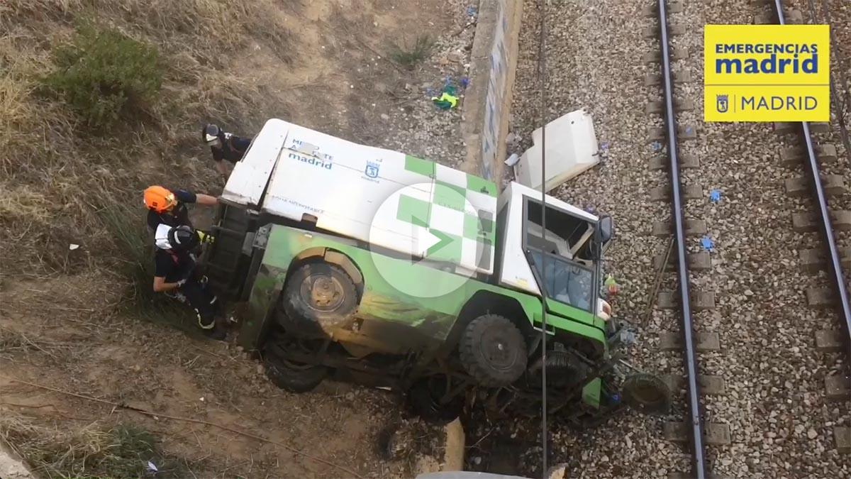 El camión de Medio Ambiente caído en las vías del tren junto al parque Juan Carlos I de Madrid.