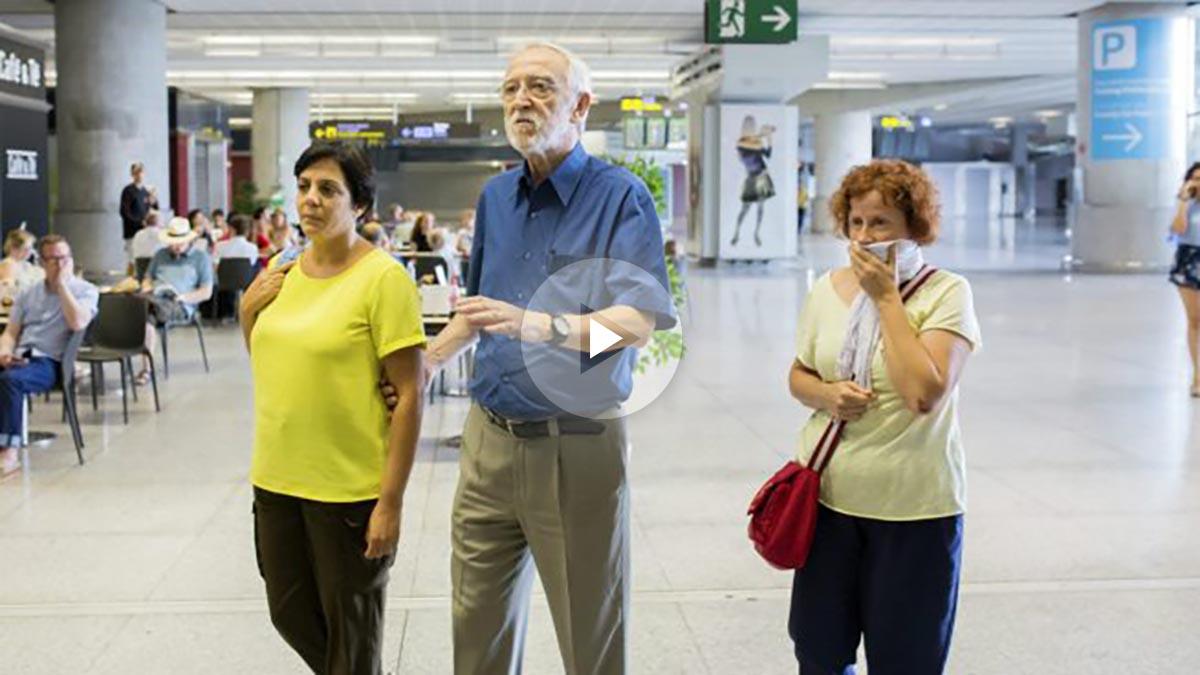 Jordi Folgado, director de la Fundación Vicente Ferrer, junto a dos de las heridas, en el aeropuerto de Málaga. (EFE)