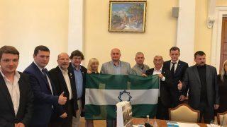 El presidente de la ANA, Pedro Ignacio Altamirano en el parlamento de Crimea  con una bandera indepedentista andaluza (Foto: Facebook)