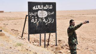 Un soldado sirio se fotografía junto a un cartel con reclamos del Estado Islámico. (Foto: AFP)