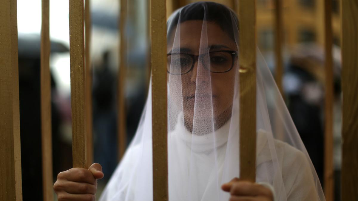 Una mujer vestida de novia protesta en una jaula a favor de los derechos de las mujeres en Beirut (Líbano). (AFP)