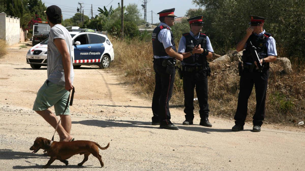 Un vecino pasa junto a su perro ante los Mossos que investigan la casa de Alcanar (Tarragona). (EFE)