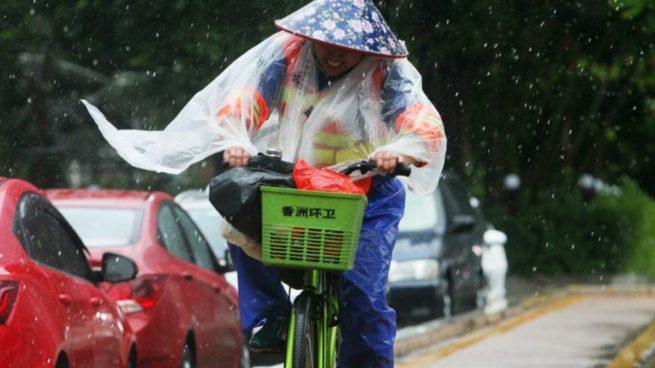 Un japonés anda en bicicleta mientras el tifón Hato hace acto de presencia. Foto: AFP