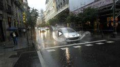 Coches circulando por una calle un día de lluvia.
