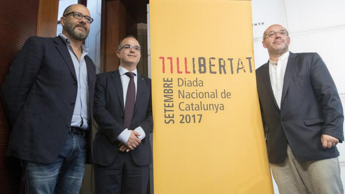 El conseller de la Presidencia y portavoz del Govern, Jordi Turull (c), y el vicepresidente primero del Parlament, Lluís Guinó (d), y el creado artístico del acto de la Diada, Josep María Mestres (i), durante la presentación de los actos institucionales de la Diada de Cataluña. Foto: EFE