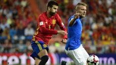 Piqué disputa un balón con Insigne. (AFP)