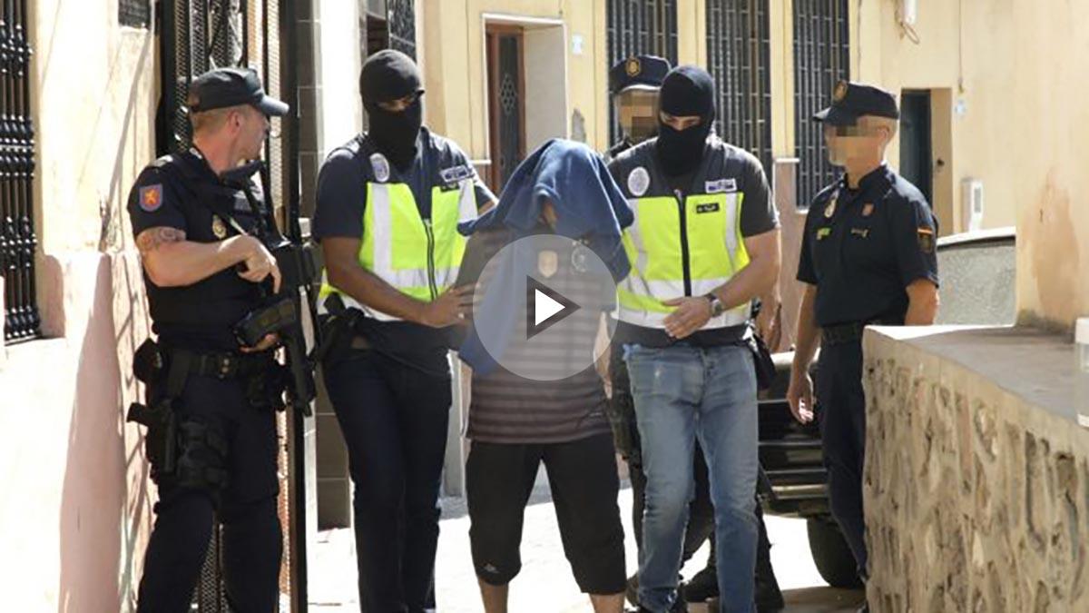 Efectivos de la Policía Nacional traslada a una persona detenida durante el registro realizado hoy en un domicilio del barrio periférico del Monte María Cristina de Melilla (Foto: Efe)